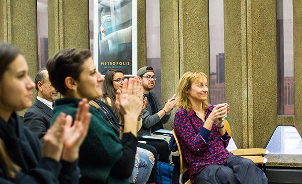 Students and faculty applaud at a presentation