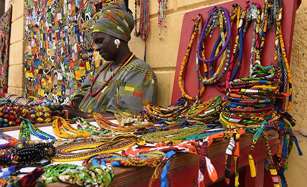 A woman sits in a market stall full of bright, beaded necklaces in Senegal.